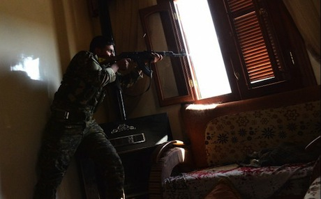 A Kurdish fighter from the People's Protection Units (YPG) fires towards Syrian government forces inside a building in the majority-Kurdish Sheikh Maqsud district of Aleppo, on April 21, 2013